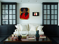 In the family room, a two-part artwork by Mickalene Thomas hangs above a custom-made sofa by Paolo Moschino that's covered in Belgian linen; the cabinets are also a custom design, and the walls are painted in Papers and Paints' Not Totally White.