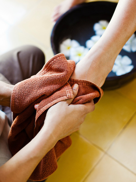 Woman receives spa pedicure at Visaya Spa, FCC Angkor, Siem Reap, Cambodia. The pedicure begins with a floral foot bath and scrub followed by a polish application.