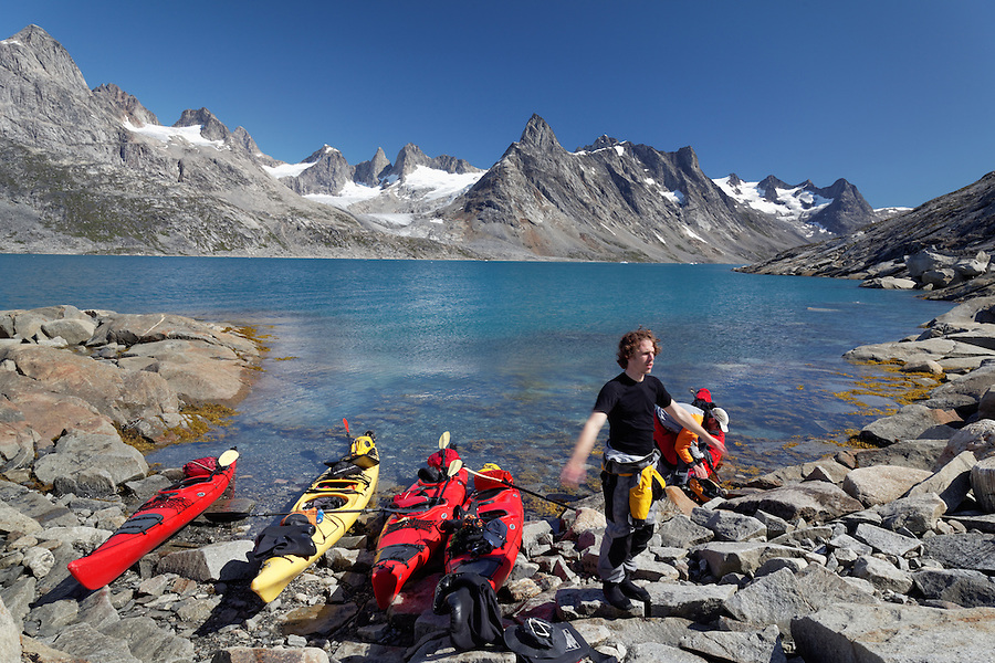 Sea kayakers taking break on beach, Ikaasatsivaq Fjord, Ammassalik Island, East Greenland