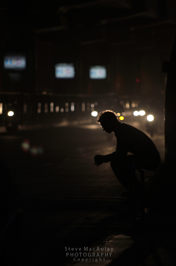 Silhouette of young man waiting alongside a busy road for a bus in downtown New Delhi, India.