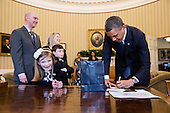 United States President Barack Obama signs memorabilia for March of Dimes 2013 National Ambassador Nina Centofanti, 8, at the Resolute Desk during her visit to the Oval Office, March 26, 2013. Centofanti's parents Vince and Christine, brother Nicholas, and sister Mia, not visible, stand behind her..Mandatory Credit: Pete Souza - White House via CNP