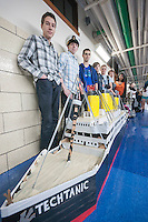 """""""Team Last Minute"""" poses with their Techtanic entry in Brooklyn Technical High School's Cardboard Boat Regatta in Brooklyn in New York on Friday, March 1, 2013. As part of Engineering Week the teams of students constructed boats made only of cardboard and duct tape. The team's assigned """"captain"""" piloted their boat from one end of the pool to the other and back in a heat with other boats, hopefully without sinking. The surviving boats were timed and the winners received bragging rights with an award also going to the most spectacular sinking. (© Richard B. Levine)"""