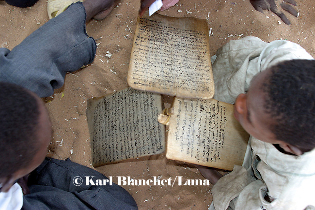 Talibes learning coranic versets written on wooden boards outside the house of the marabout in Maradi, Niger. In Niger, coranic schools still exist and are very traditional. Talibe, pupils, even go and beg for money and food in the afternoon in order to pay the marabout.