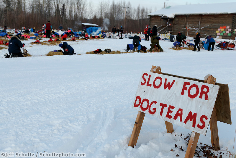 A slow sign sits next to the road where the teams are parked outside the community center at Tanana on March 10, 2015.   2015 Iditarod.<br /> <br /> (C) Jeff Schultz/SchultzPhoto.com - ALL RIGHTS RESERVED<br />  DUPLICATION  PROHIBITED  WITHOUT  PERMISSION