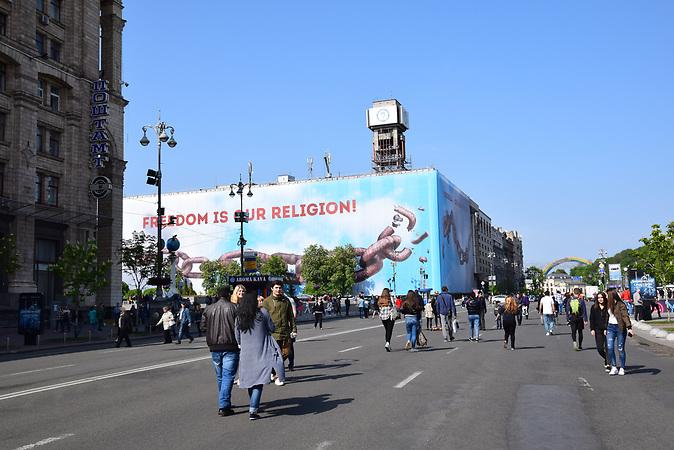 """ESC Vorbericht <br />Ein paar Tage vor dem ESC in der Innenstadt von Kiew: <br />Der neu angebrachte Slogan """"Freedom is our religion"""" auf dem Maidan in Kiew. Das Banner verdeckt das immer noch nicht renovierte Gewerkschaftshaus, welches während der Revolution 2013-2014 als Hauptquartier der Demonstranten diente und in der Nacht vom 18. auf den 19. Februar nahezu komplett ausbrannte."""