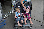 A woman feeds her child in a double-wide stroller, one of many such large strollers which locals say are a trend characteristic of Lincoln Park and Old Town, on North Wells Street, the main shopping thoroughfare in Old Town, in Chicago, Illinois on June 19, 2009.
