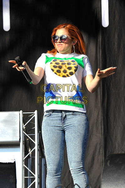 Katy B (Kathleen Anne Brien).performing at 'As One In The Park' festival, Victoria Park, London, England. 26th May 2013.on stage in concert live gig performance music half length hands arms funny white top sunglasses shades blue green leopard print jeans denim.CAP/MAR.© Martin Harris/Capital Pictures.