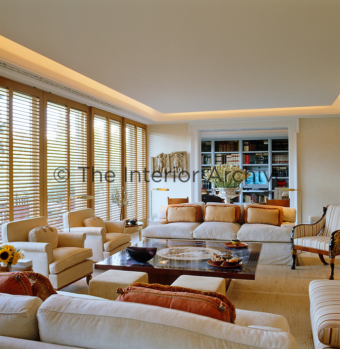 The living room opens onto the library and the windows are screened with custom-made oak shutters to diffuse the light