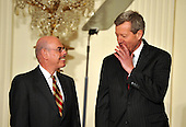 "Washington, D.C. - March 2, 2009 -- United States Senator Max Baucus (Democrat of Montana), Chairman, Senate Finance Committee, right, seems to be sharing a secret with United States Representative Henry Waxman (Democrat of California), Chairman, House Energy and Commerce Committee as they await the arrival of  United States President Barack Obama in the East Room of the White House in Washington, DC on Monday, March 2, 2009.  In later remarks the President named Governor Kathleen Sebelius (Democrat of Kansas) as Secretary of the Department of Health and Human Services (HHS).  The President also announced the release of $155 million authorized by the American Recovery and Reinvestment Act (ARRA) that will support 126 new health centers.  In a release, the White House stated ""These health centers will help people in need - many with no health insurance - obtain access to comprehensive primary and preventive health care services."".Credit: Ron Sachs / Pool via CNP"