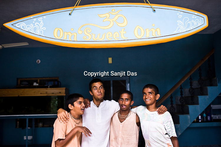 """(Left to right) Satyaraj, Daruka, Kirtan Ananda and Dicky are seen with the surfboard with the pun on the title, Home Sweet Home in the their own verison of Om Sweet Om at the Kaliya Mardana Krishna Ashram in the coastal town of Mulki, just north of Mangalore, Karnataka, India.  ..Krishna devotees in the Gaudiya Vaishnava tradition of Hinduism, they are known collectively as the """"surfing swamis."""" The """"surfing ashram"""" is growing in popularity and surfing here is a form of meditation, a spiritual practice leading to heightened states of awareness."""