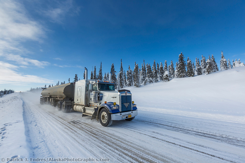 Industrial truck carries supplies along the icy James Dalton Highway in winter.