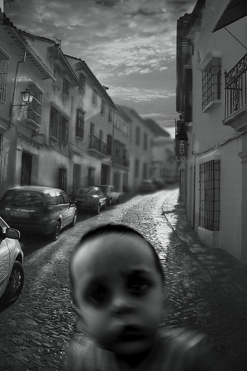 A young boys face looking directly into the camera on a cobbled street in Spain