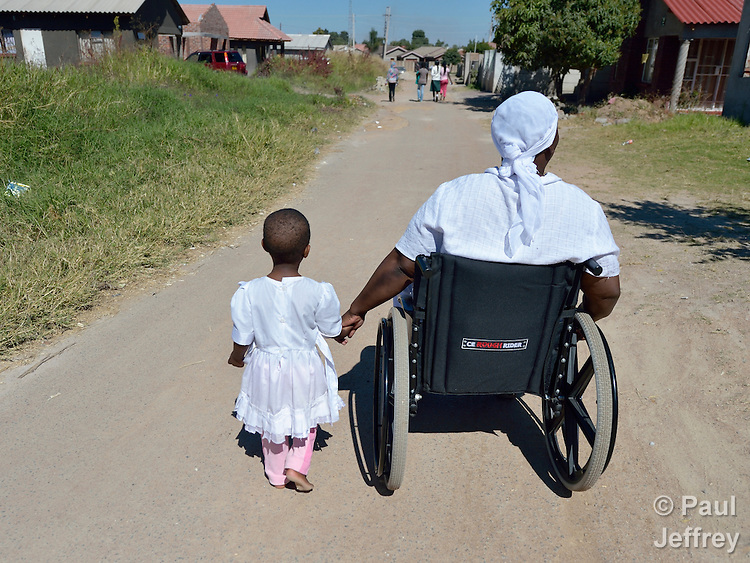 Jennifer Mhlanga suffered a spinal injury in a bus accident, and today uses a wheelchair to get around Harare, Zimbabwe. Here she moves along a street in her neighborhood with her three-year old granddaughter, Tariro Bvumakurehwa. Mhlanga's wheelchair, which was carefully fitted to her individual needs, was provided by the Jairos Jiri Association with support from CBM-US.