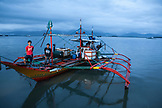 PHILIPPINES, Palawan, Puerto Princesa, fishermen stand on their boat in the City Port Area