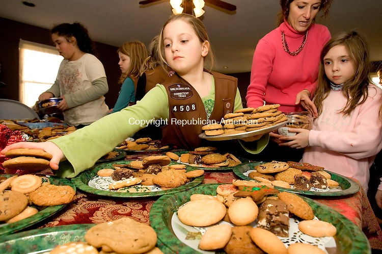 BETHLEHEM, CT- 19 DECEMBER 2006-121906JS04-Emmalee Levesque, center, a member of Girl Scout Troop 4508 from Bethlehem/Woodbury, loads up trays of cookies with the help Scout leader Donna Munson and scout Julia Walters, load up cookie platters on Tuesday as the troop makes gift packs for shut-ins in the town of Bethlehem. The goods will be distributed by the Bethlehem Lions Club.<br /> Jim Shannon/Republican-American