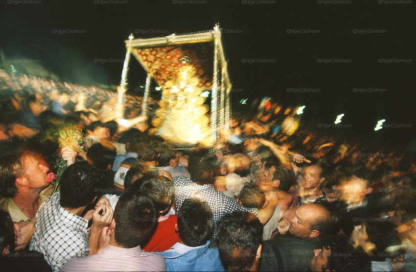"The Virgin of El Rocio, or Madonna de El Roco is carried by Hermandades brotherhoods around the town from after midnight until after midday the Monday of the Rocio weekend. El Rocio, Huelva Province, Andalusia, Spain...El Rocio follows on from Semana Santa - Easter week and the various spring ferias, of which Seville's Feria de Abril (April) is the biggest. The processions to the (Hermitage) Hermita de El Rocío, at Pentecost, is the most famous (Romeria) pilgrimage in the Andalusian region, attracting nearly a million people from across Andalusia, Spain and the world. The cult started off in the 13th century when a statue of the virgin Mary was apparently found in a tree trunk in the Donana Park. What was first a local devotion at Pentecost by local pilgrim brotherhoods ""hermandades"" became by the 19th century into dozens of fraternities developed from such as Cadiz, Selville and Huelva. Some walk for several days, others travel with oxen drawn wagons or on horseback, with traction engines and all terrain vehicles, camping along the trail they take. They wear Andalusian costumes, tight breeches, boots, short jackets and frilly flamenco skirts. Many festivities, flamenco dance, laments, songs and music are combined with religious prayers. Devout pilgrims walk as a penance, keeping vows of silence. An emblem of the immaculate conception (sin peche) is carried. On the Pentecost after the stroke of midnight on the whit Sunday the virgin Mary is carried from the church through the streets of El Rocio by each hermandade to visit each brotherhood's shrine."
