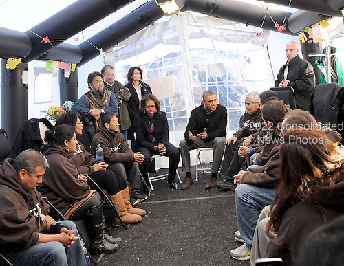 United States President Barack Obama and first lady Michelle Obama meet 18 people who have been fasting for a day two people who have been fasting for 18 days as part of the Fast For Families on the National Mall in support of immigration reform, on Friday, November 29, 2013, in Washington, D.C.  Eliseo Medina is seated to the President's left and Dae Joong Yoon is seated to the First Lady's right.<br /> Credit: Leslie E. Kossoff / Pool via CNP