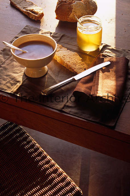 A shaft of sunlight floods a place setting for a simple breakfast of coffee, bread and honey