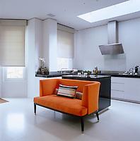 An orange sofa adds a splash of colour to this minimal kitchen.