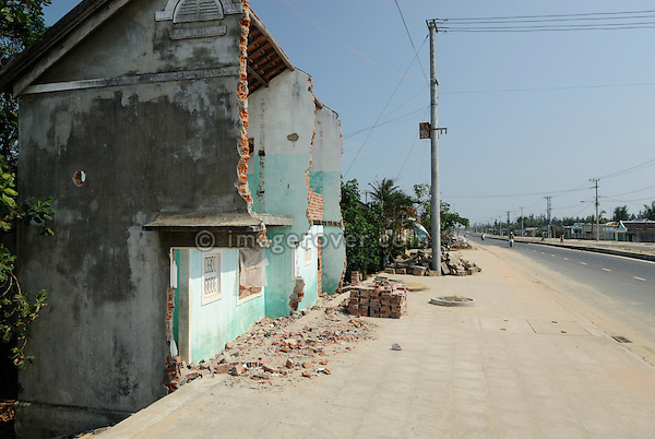 Asia, Vietnam, nr. Hoi An. Along the coastal road between Hoi An and Da Nang, homes were cut in half to make space for the new now wider road ....
