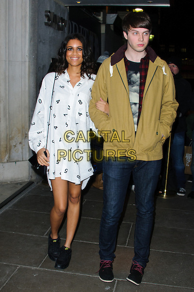 Aluna Francis and George Reid of Alunageorge.Brits 2013 Nominations Party - Outside Arrivals, London, United Kingdom,.10th January 2013..full length white print dress shirt  numbers  jeans mustard jacket  band group .CAP/CJ.©Chris Joseph/Capital Pictures.