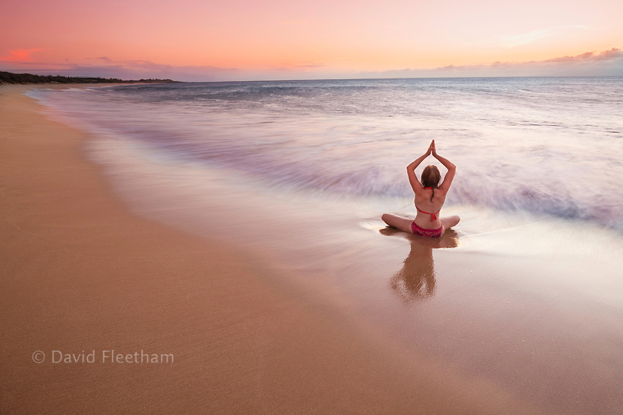 A woman (MR) holding a yoga position at sunset on Papohaku Beach on the far western end of the island of Molokai, while the sun sets behind Oahu on the horizon. This is one of the longest white-sand beaches in the Hawaiian Islands.