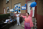 Pro-Scottish independence supporter Karen Clarkson waving to passers-bay watched by Ann Shields  in the front of their house in Cardonald, Glasgow on the day of the independence referendum. Yes Scotland were campaigning for the country to leave the United Kingdom, whilst Better Together were campaigning for Scotland to remain in the UK. On the 18th of September 2014, the people of Scotland voted in a referendum to decide whether the country's union with England should continue or Scotland should become an independent nation once again and leave the United Kingdom.