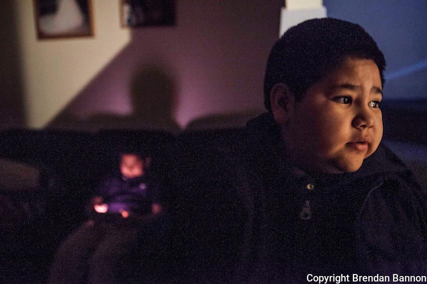 Manuel Maldonado, age 11, plays games on a tablet while his younger brother Jonathan, age 9, prepares for school in Painesville, Ohio.  Their mother work shift begins at 5 AM. The brothers wake themselves at 6:45 everyday and get ready for school before being seen off to the bus by thier elder brothers. Brendan Bannon. Painesville, Ohio, March 26, 2014
