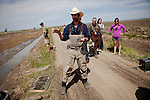 California Trout's Jacob Katz, center, talks to members of the media in a rice field on Knaggs Ranch near Woodland, California, March 23, 2013. Research by UC Davis Center for Watershed Sciences, conservation science and advocacy organization California Trout, and the California Department of Water Resources shows that salmon raised in a floodplain have higher growth rates than those in a river or hatchery.