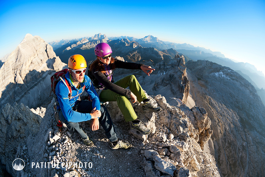 A couple sitting on the summit of the Punta Fanes in the Italian Dolomites after climbing the Via Ferrata Tomaselli