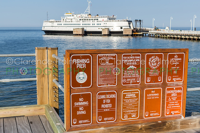A sign outlines the rules for using the fishing pier in Oak Bluffs, Massachusetts in Martha's Vineyard.  In the background, a Steamship Authority ferry waits to depart for the trip back to Woods Hole on the mainland.