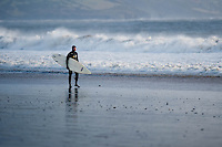 Friday 03 January 2014<br /> Pictured: A surfer walks along Saundersfoot Beach, West Wales<br /> Re: Storm force winds and some of the highest tides in decades hit Wales early on Friday.