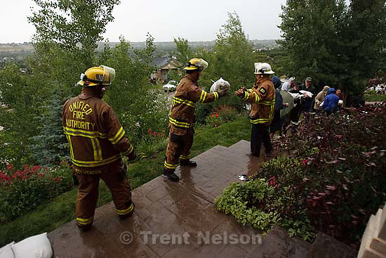 Draper - Firefighters and volunteers try to stop storm runoff from washing away Frank Maylett's home on Bear Mountain Drive, Saturday, June 20, 2009.