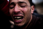 "Abdul Farj 25, cries uncontrollably during a funeral procession for his fallen brother, a volunteer fighter for the revolution killed by Pro-Gadafi forces while retreating from the oil-producing city of Ras Lanuf. ""My brother, you're free now,"" he cried. Benghazi, Libya. March 9, 2011."