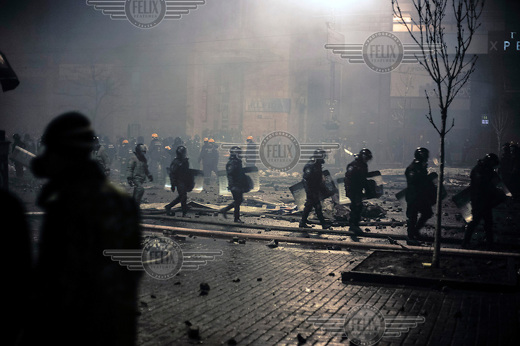 Riot police march in single file through the detritus left on the street after weeks of protest in central Kiev. Protests against the government of President Viktor Yanukovych were sparked on 21 November 2014 by the Ukrainian government's decision to suspend preparations for the signing of an association agreement with the European Union that would have increased trade with the EU. Some believe that the U-turn came about as a result of pressure from President Putin of Russia who wants Ukraine to join a customs union with itself, Kazakhstan and Belarus. Russia offered 15 billion dollars of soft loans and reduced price gas to Ukraine at the same time as discussions with the EU were taking place. After weeks of protests and a number of deaths, Prime Minister Mykola Azarov and the entire cabinet resigned. Protesters are holding out, however, for President Yanukovych to resign and continue to occupy public buildings and squares to put pressure on the president. On 18 February, after Yanukovych's party scuppered a move to change the constitution to reduce the powers of the president, renewed fighting between protesters and police broke out and had cost the lives of around 80 people by Friday 21st February.