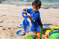 Young Local Hawaiian boy playing with toys in the sand on the beach on Oahu in Hawaii