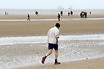 Cunard Line's Three Queens Meeting Liverpool. <br /> Crosby Beach 25.5.15 A jogger on the beach with Queen Elizabeth and Queen Victoria visible out at sea.