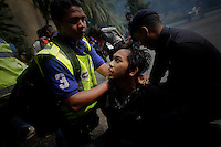 "A supporter of the ""Bersih"" electoral reform coalition looks at a policeman as he is being detained during clashes in downtown Kuala Lumpur July 9, 2011. Malaysian police fired tear gas and detained more than 500 people in the capital on Saturday in a bid to prevent thousands of anti-government protesters from putting on a massive show of strength against Prime Minister Najib Razak.  REUTERS/Damir Sagolj (MALAYSIA)"