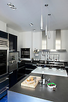 The kitchen is a sleek combination of black granite, stainless steel and dark blue lacquer