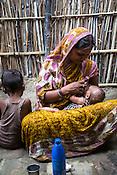 Maina Devi breastfeeds her 3 month old daughter, Priya in the courtyard of their hut in Bhelaiya village in Raxaul, Bihar, India.