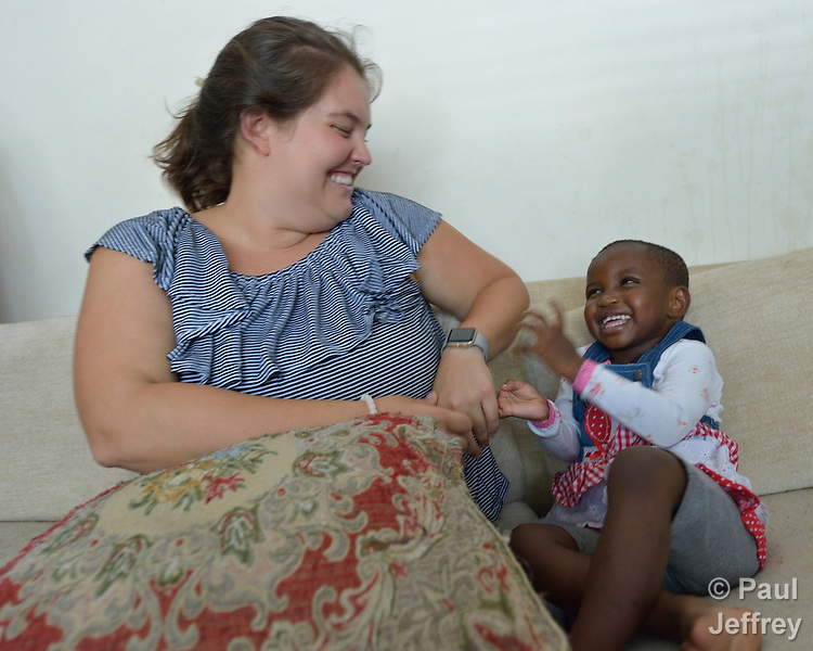Krista Camp, a case manager for Church World Service, plays with Rehema, a child from the Democratic Republic of the Congo, during a visit to her family's apartment in Durham, North Carolina. <br /> <br /> Church World Service resettles refugees in North Carolina and throughout the United States.<br /> <br /> <br /> Photo by Paul Jeffrey for Church World Service.