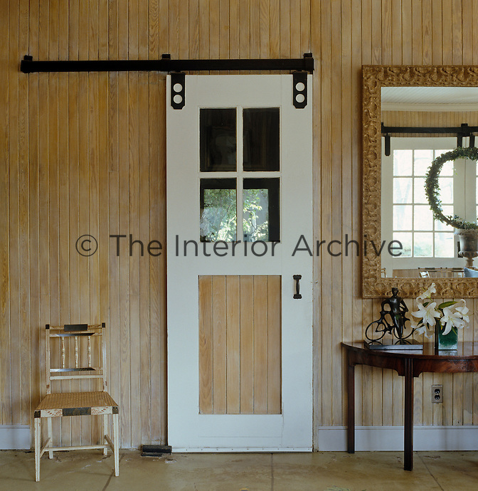 A chair sits next to a stable-style sliding door in this wood-clad entrance hall
