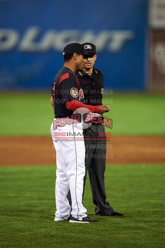 Batavia Muckdogs manager Angel Espada (4) questions a call with umpire Donnie Smith during a game against the Auburn Doubledays July 10, 2015 at Dwyer Stadium in Batavia, New York.  Auburn defeated Batavia 13-1.  (Mike Janes/Four Seam Images)