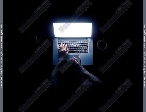 Woman using a laptop computer in darkness with her hands illuminated by the computer screen isolated on black background