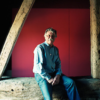 Portrait of architect David Pocknell sitting on a large beam in his barn conversion