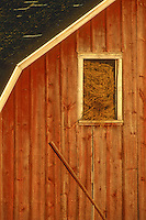 An Amish barn bursts with hay through an loft window while a crooked board shows need of some repair, Fillmore County, Minnesota