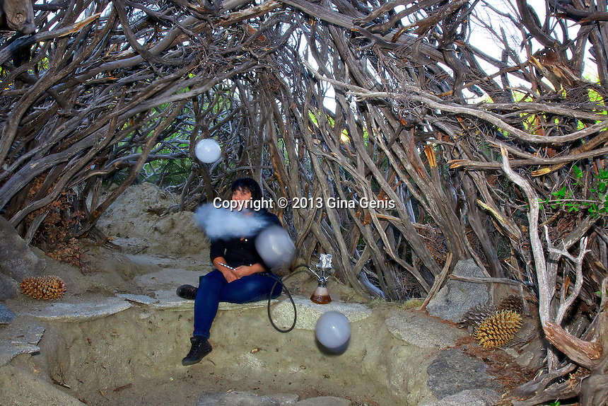 Velma Figueroa inside the Wigwam at Inspiration Point smoking her hookah and blowing bubbles.