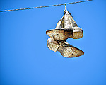 Pair of worn out cowboy boots hanging from a wire on Sixth Street in Austin.