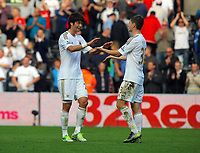 Saturday, 20 October 2012<br /> Pictured L-R: Fellow players Ki Sung Yueng and Ben Davies congratulate each other after the final whistle.<br /> Re: Barclays Premier League, Swansea City FC v Wigan Athletic at the Liberty Stadium, south Wales.