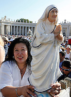 Una donna mostra alcune foto di Madre Teresa in Piazza San Pietro in occasione della messa celebrata da Papa Francesco per la sua canonizzazione, Citta' del Vaticano, 4 settembre 2016.<br /> A woman shows some photos of Mother Teresa in St. Peter's Square during a mass celebrated by Pope Francis for her canonization, at the Vatican, 4 September 2016.<br /> <br /> UPDATE IMAGES PRESS/Riccardo De Luca<br /> <br /> STRICTLY ONLY FOR EDITORIAL USE
